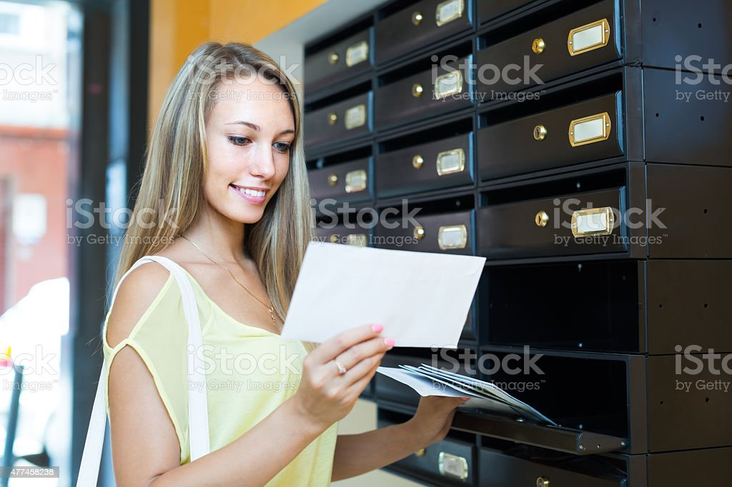 Young girl near posting box stock photo