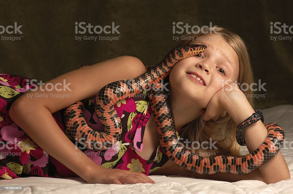Young girl nervous while holding a colorful snake. stock photo