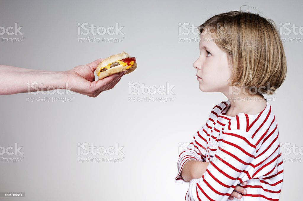 Young Girl Not Happy About Eating an Unhealthy Burger stock photo