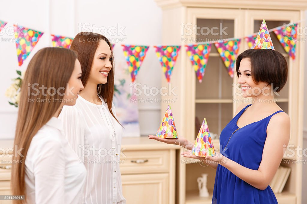 Young girl offering party hats for her friends stock photo
