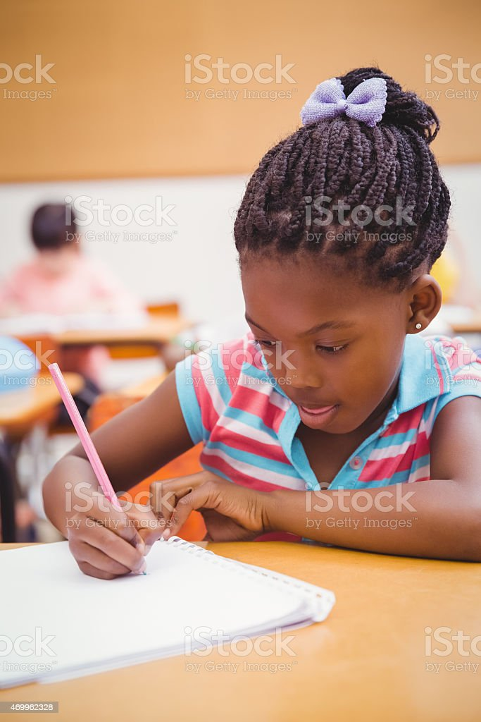A young girl on a classroom writing at her desk stock photo