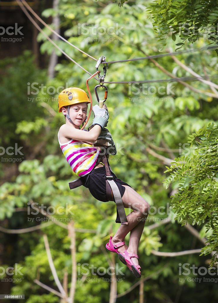 Young girl on a jungle zipline stock photo