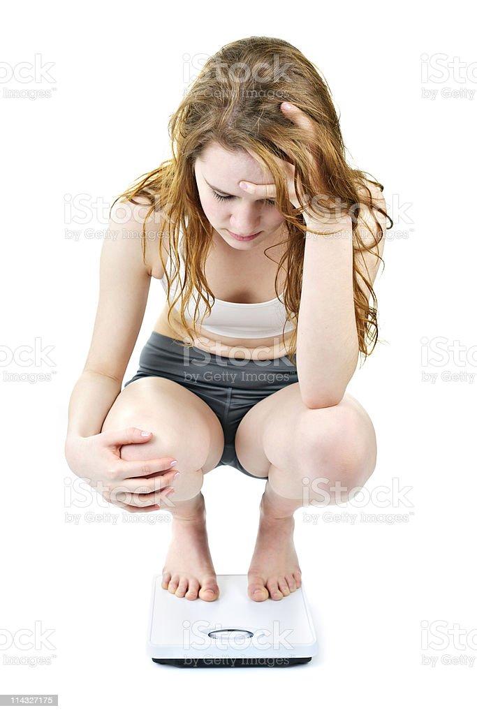 Young girl on bathroom scale looking upset stock photo