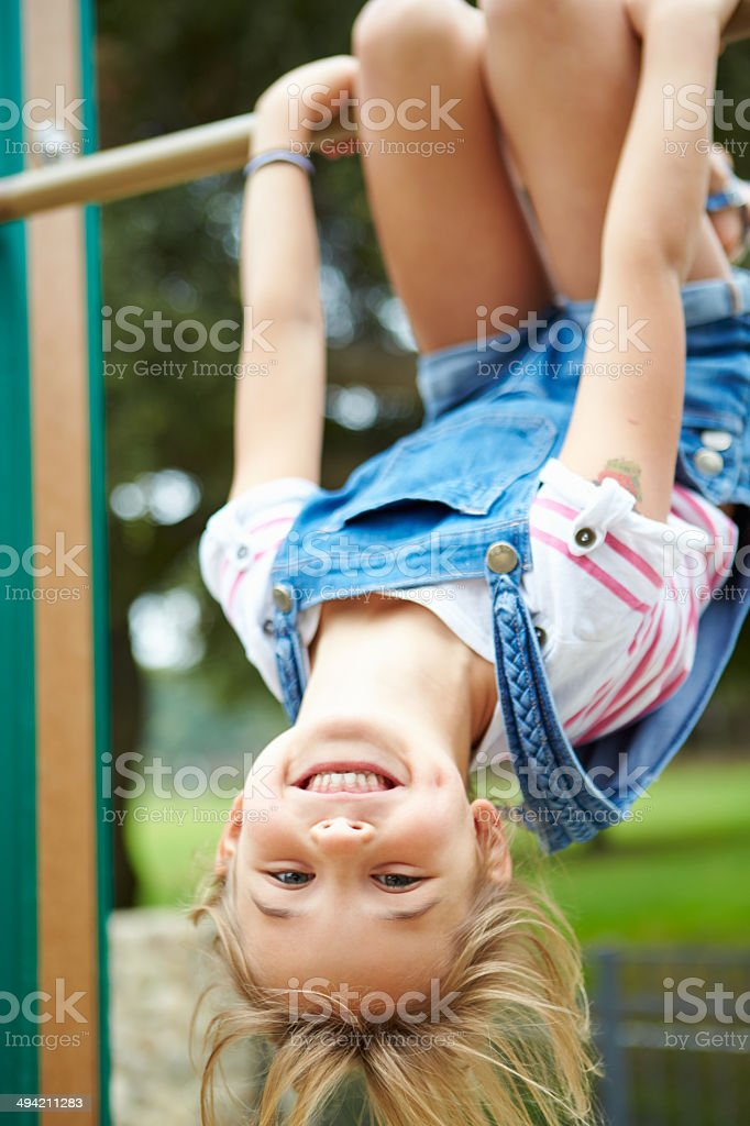 Young Girl On Climbing Frame In Playground stock photo