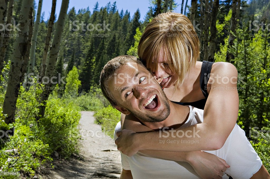 Young girl on piggyback with boy biting his ear royalty-free stock photo