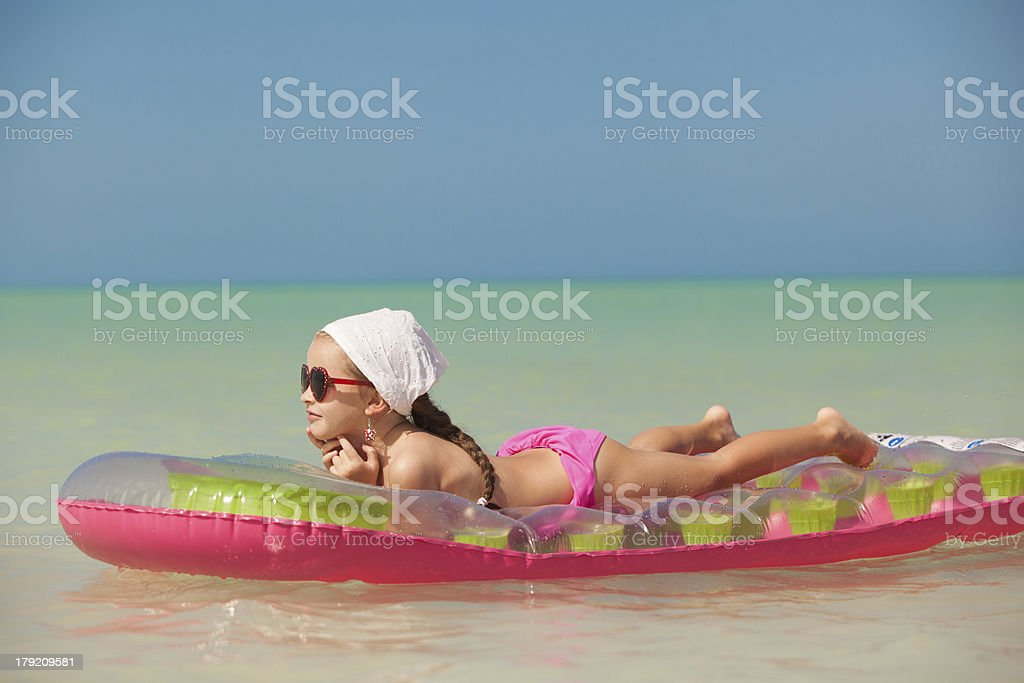 Young girl on pink air-bed in Caribbean vacation royalty-free stock photo