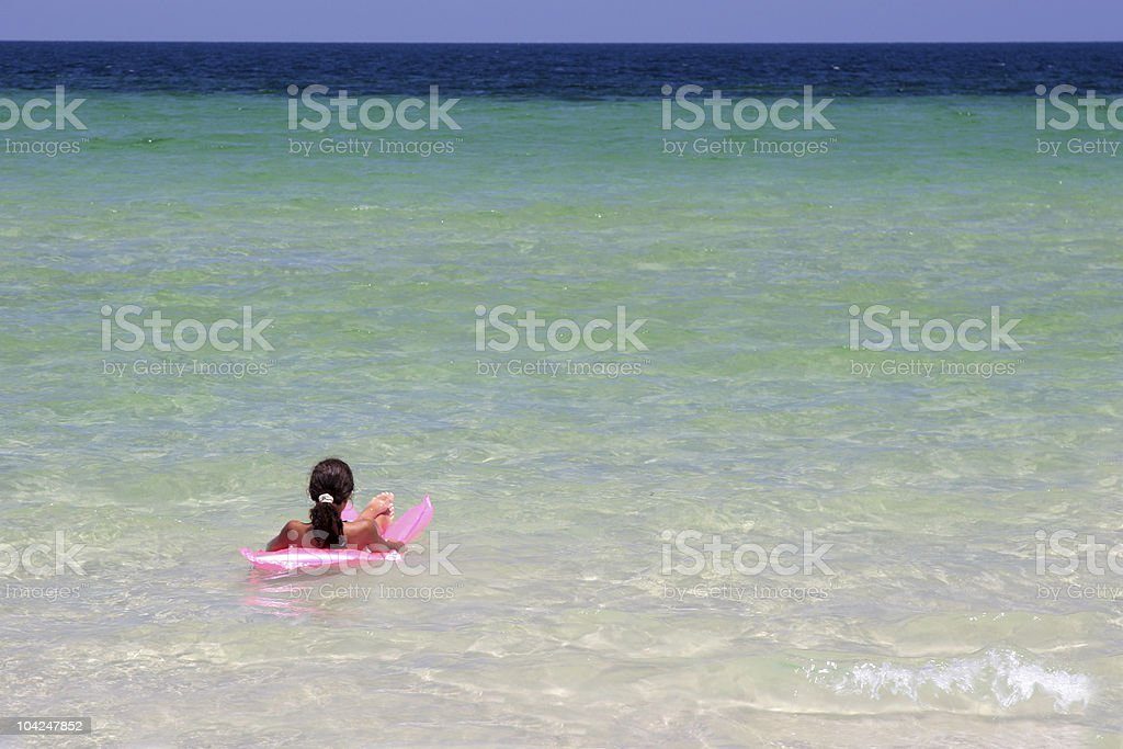 Young girl on pink air-bed in the sea royalty-free stock photo