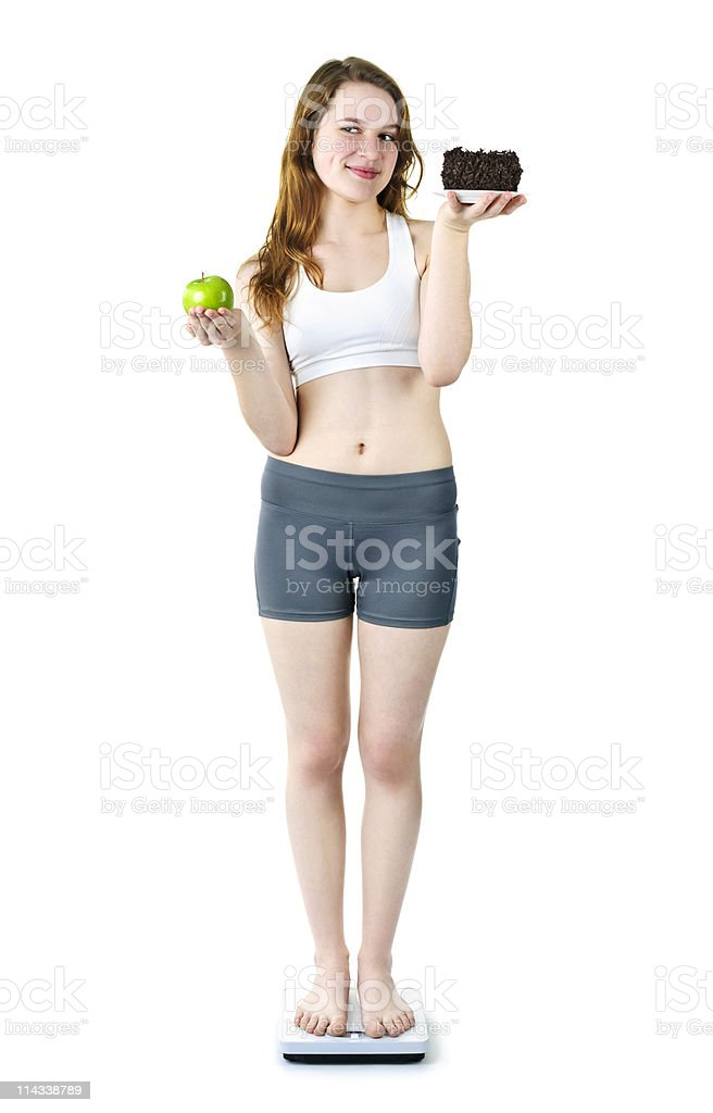 Young girl on scale holding apple and cake royalty-free stock photo