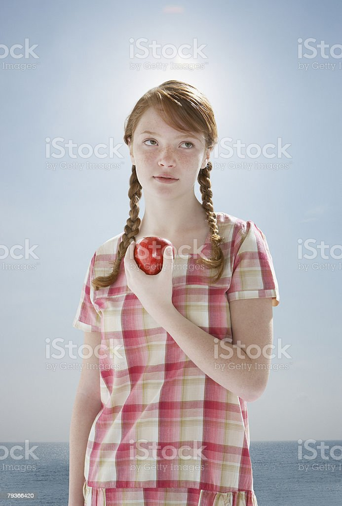 Young girl outdoors at a beach holding an apple royalty-free stock photo