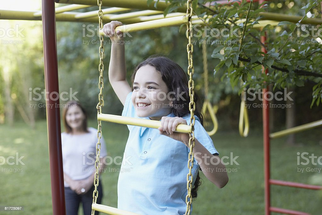 Young girl outdoors at playground climbing with senior woman in background smiling stock photo