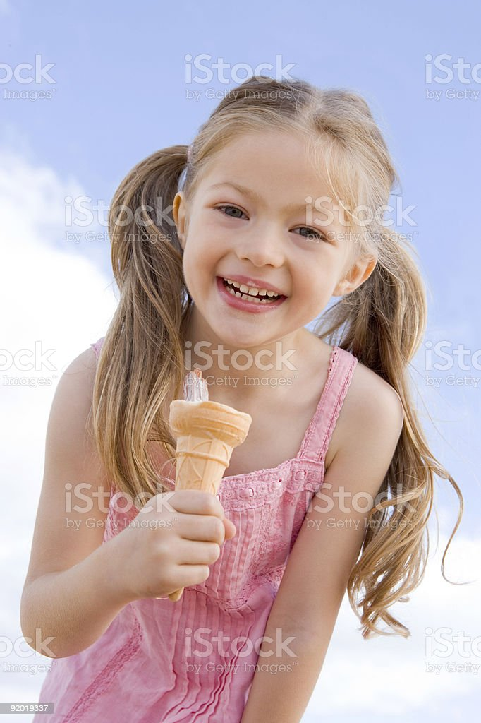 Young girl outdoors eating ice cream cone royalty-free stock photo