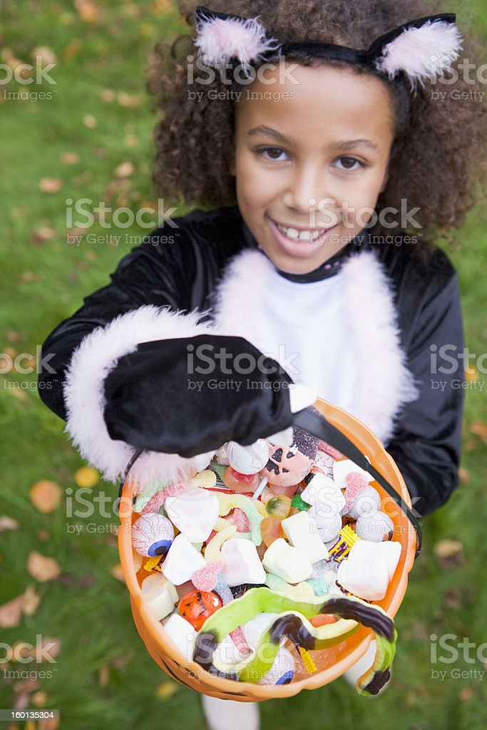 Young girl outdoors in cat costume on Halloween holding candy stock photo
