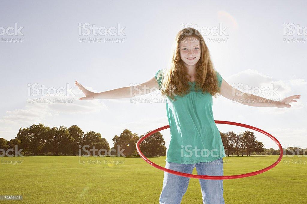 Young girl outdoors using hula hoop at a park royalty-free stock photo