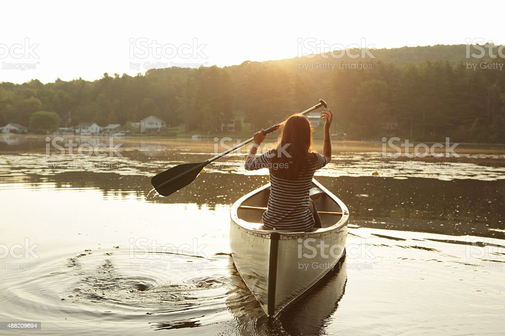 Young girl paddling a canoe as the sun rises stock photo