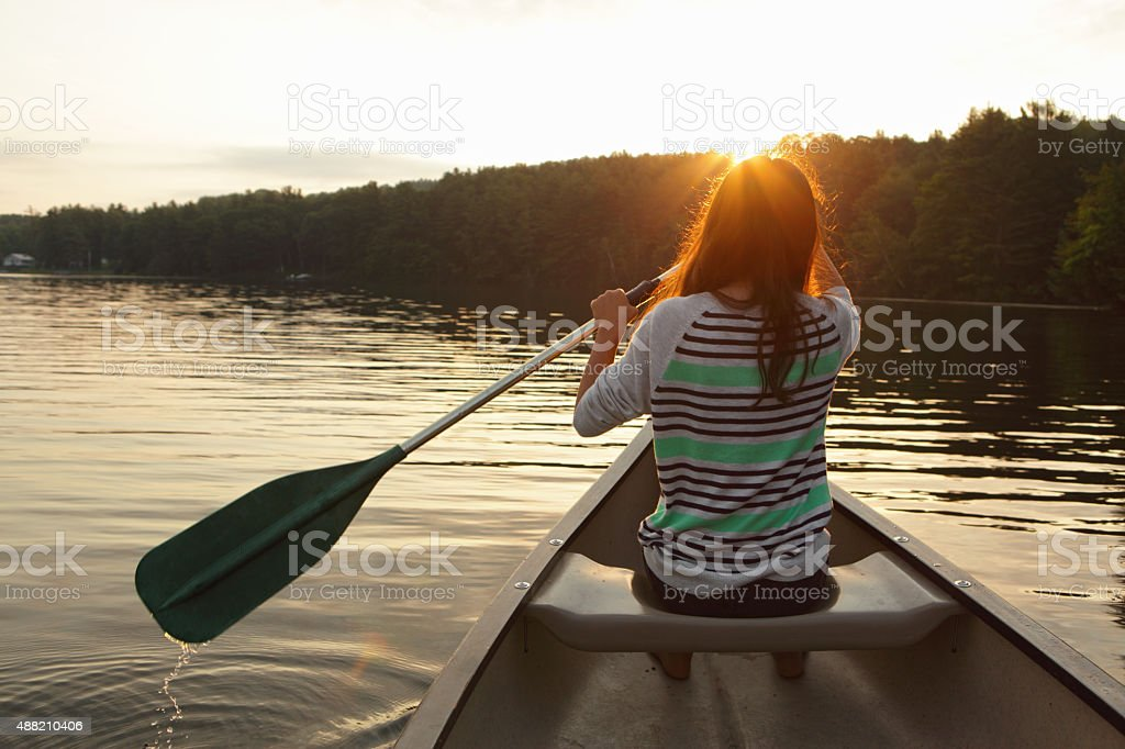 Young girl paddling a canoe on a misty lake stock photo