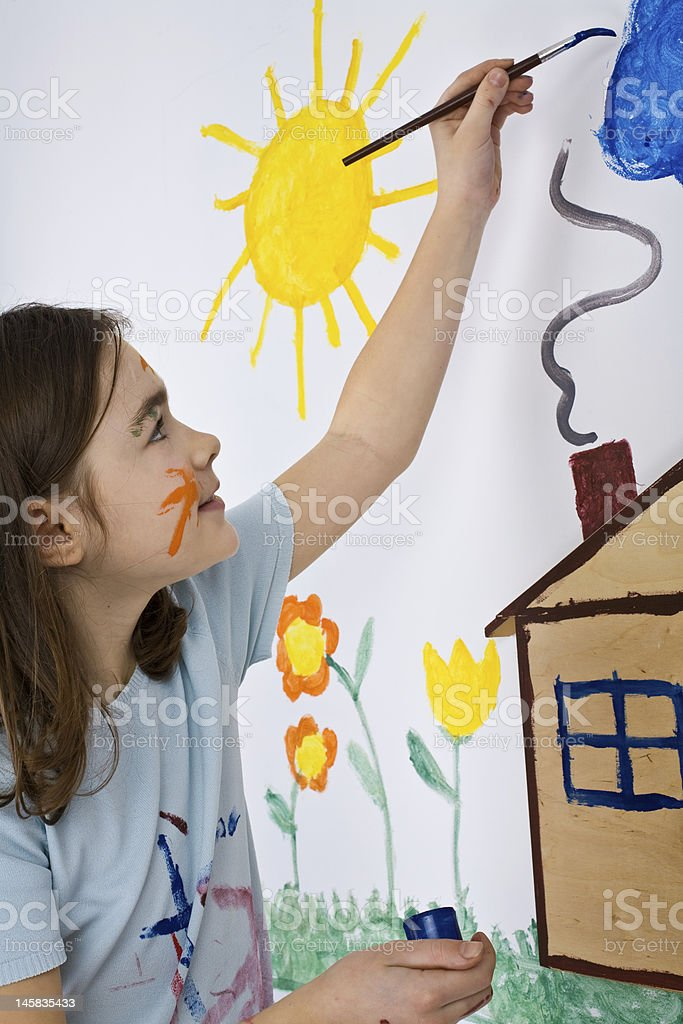 A young girl paints a house and sun on a white canvas  royalty-free stock photo