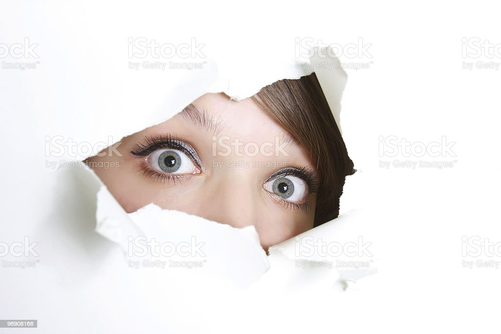 young girl peeping through hole in paper stock photo