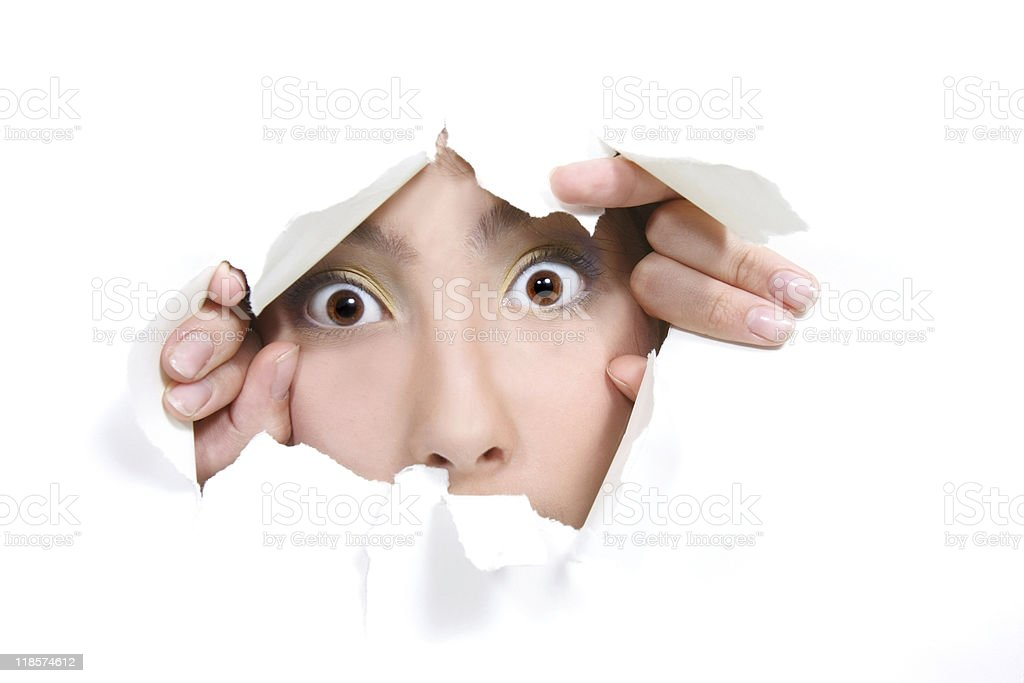 young girl peeping through hole in white paper stock photo