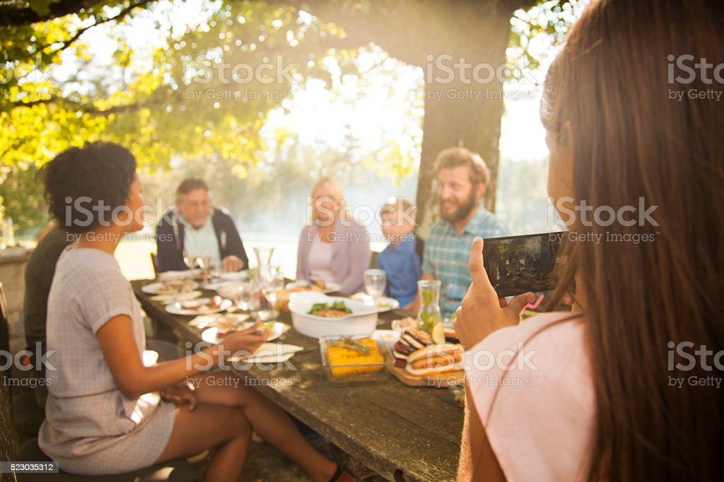 Young girl photographing her family picnic stock photo