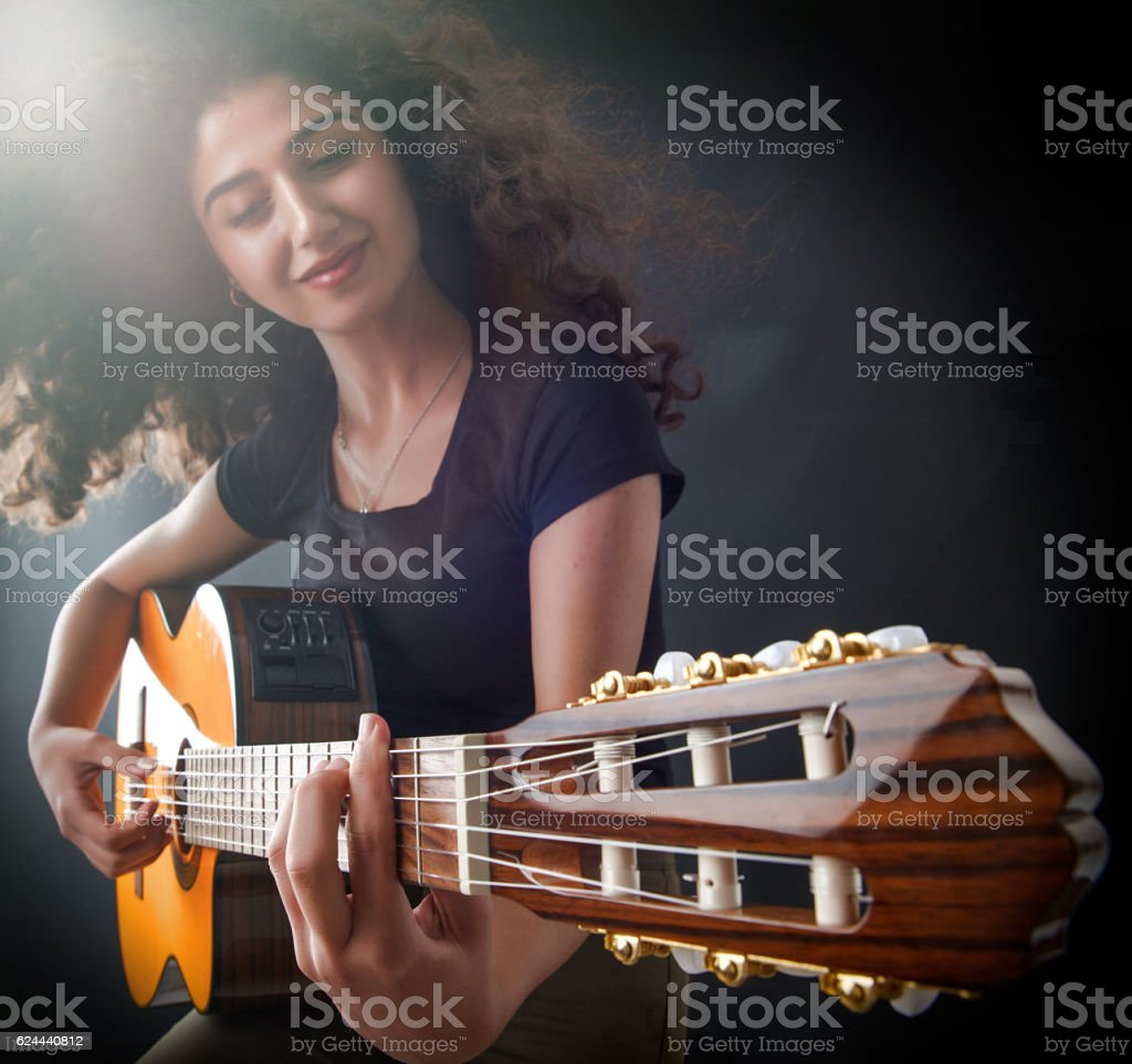 Young Girl playing a guitar during a concert stock photo