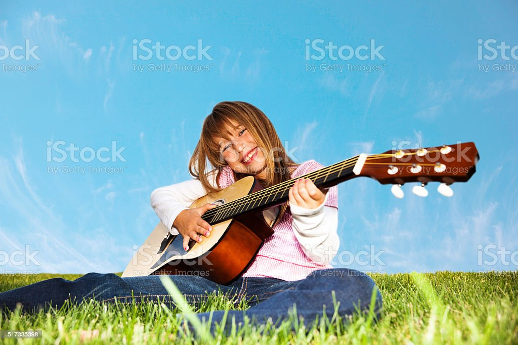 Young Girl Playing acoustic guitar outdoors stock photo