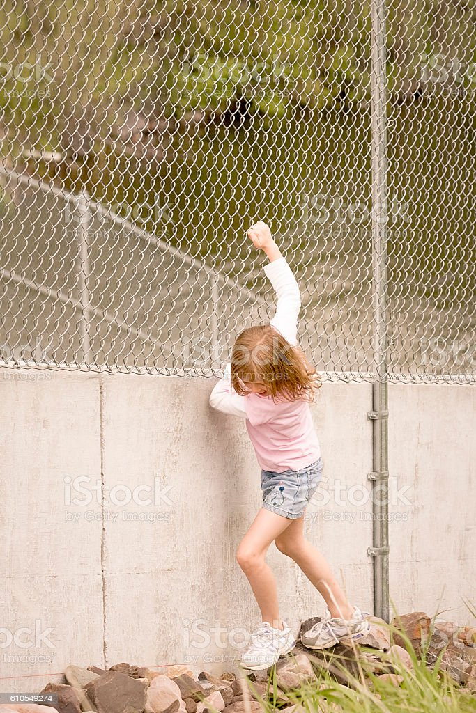 Young girl playing and clinging to fence. stock photo