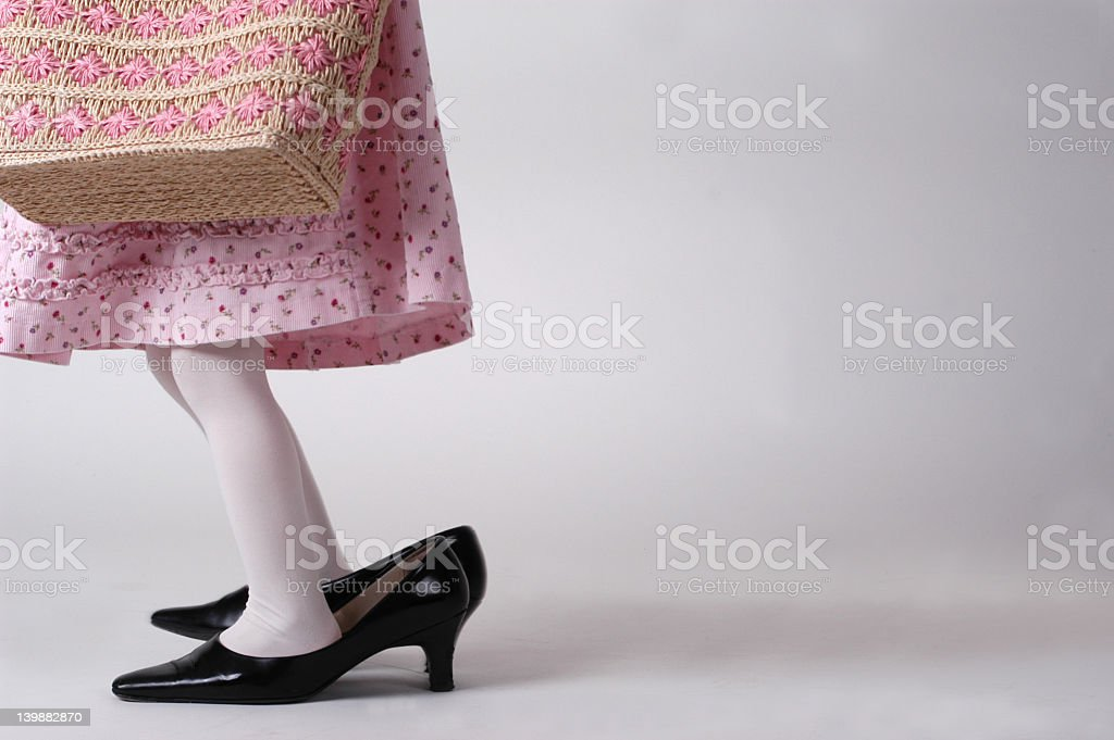 Young girl playing dress up with adult clothes stock photo