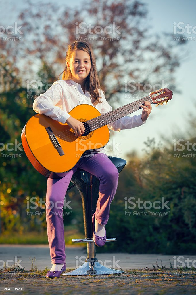 Young girl playing guitar outdoors stock photo