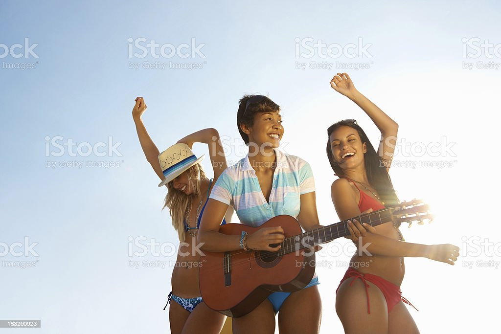 Young girl playing guitar while her friends dancing against sky royalty-free stock photo