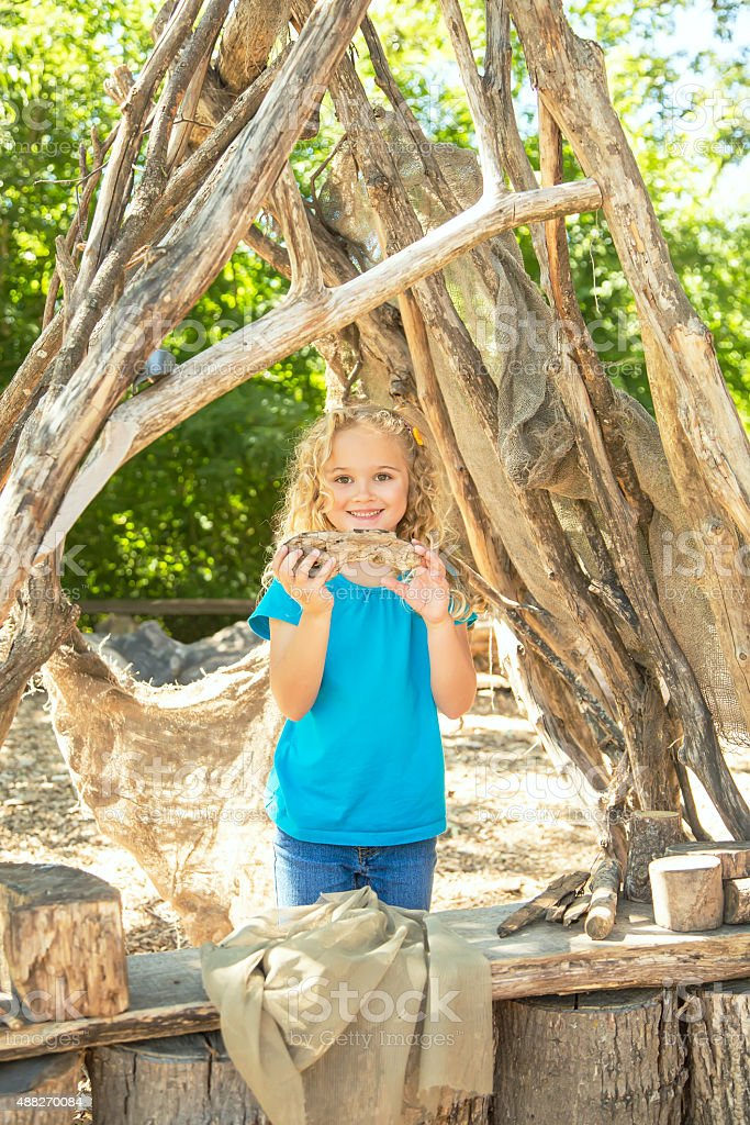 Young Girl Playing In 'Green' Nature Fort stock photo