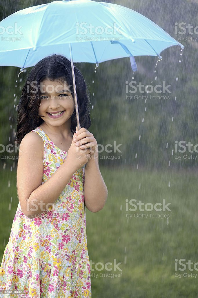 young girl playing in rain with umbrella royalty-free stock photo