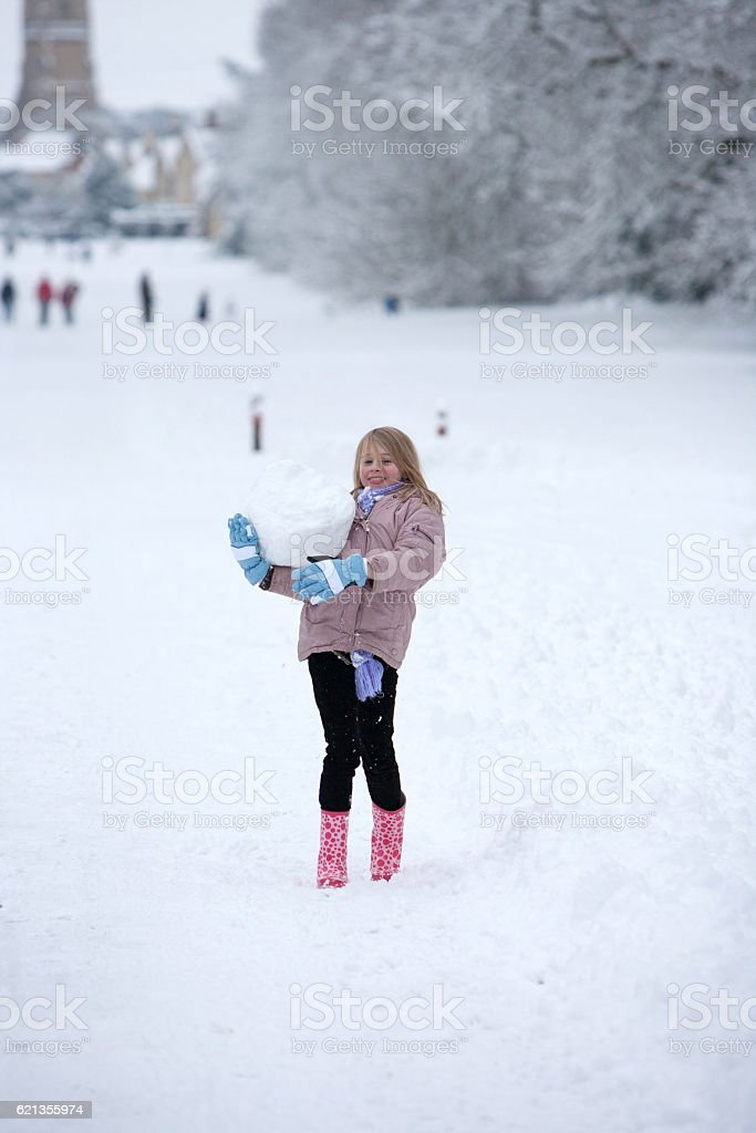 Young girl playing in snow with a large snowball stock photo