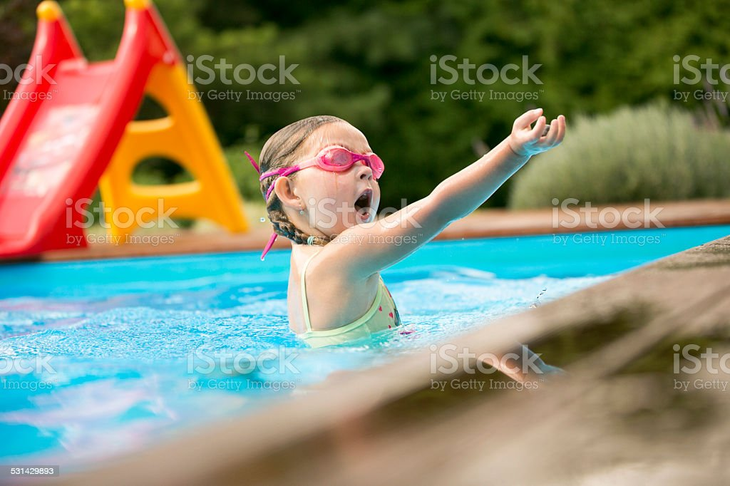 Young girl playing in swimming pool stock photo