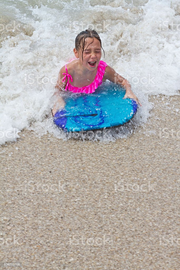 young girl playing in the sea with surfboard stock photo