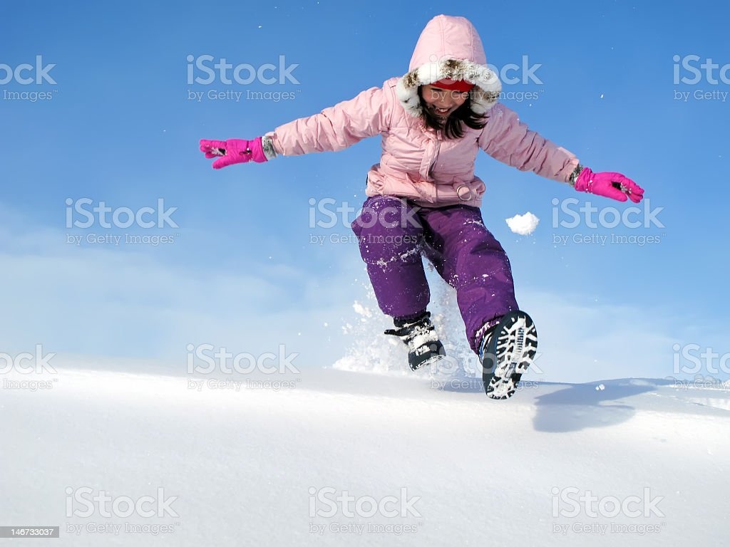 A young girl playing in the snow with snow gear on royalty-free stock photo