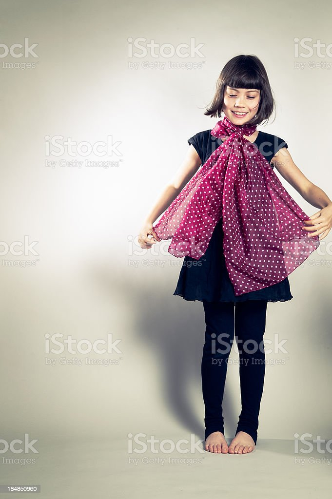 Young girl playing with a polka dot red scarf. royalty-free stock photo