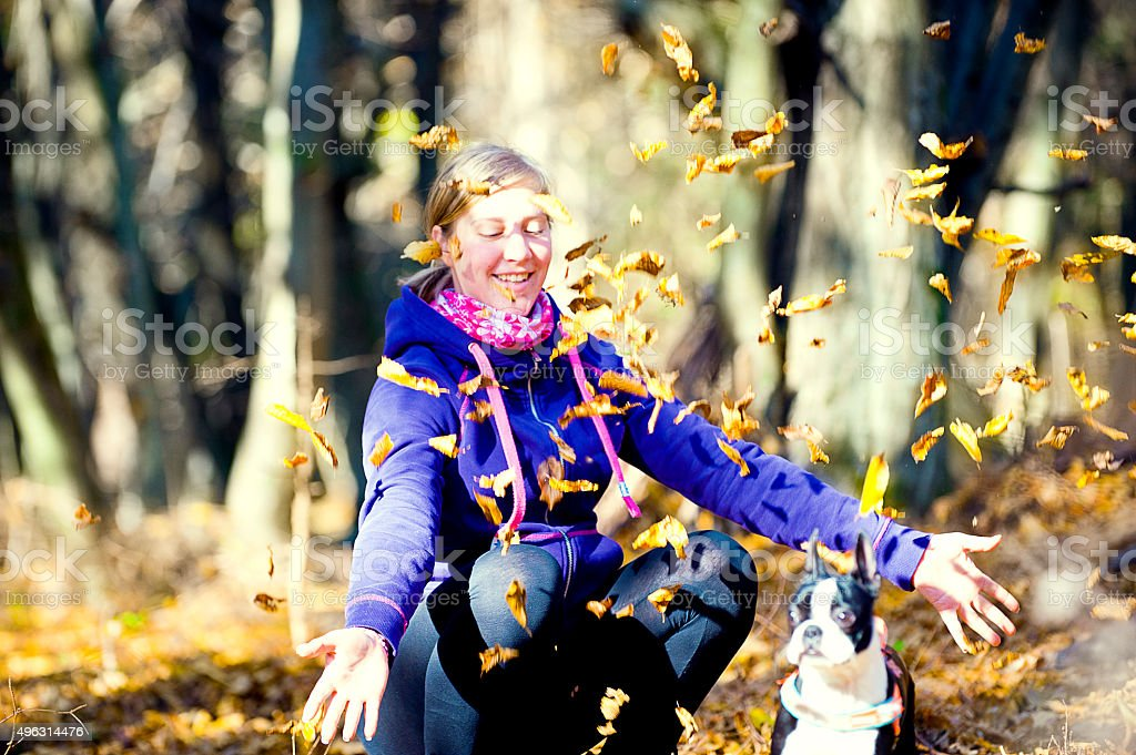 Young girl playing with autumn leaves stock photo