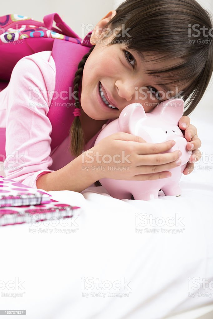 Young girl playing with her piggy bank royalty-free stock photo