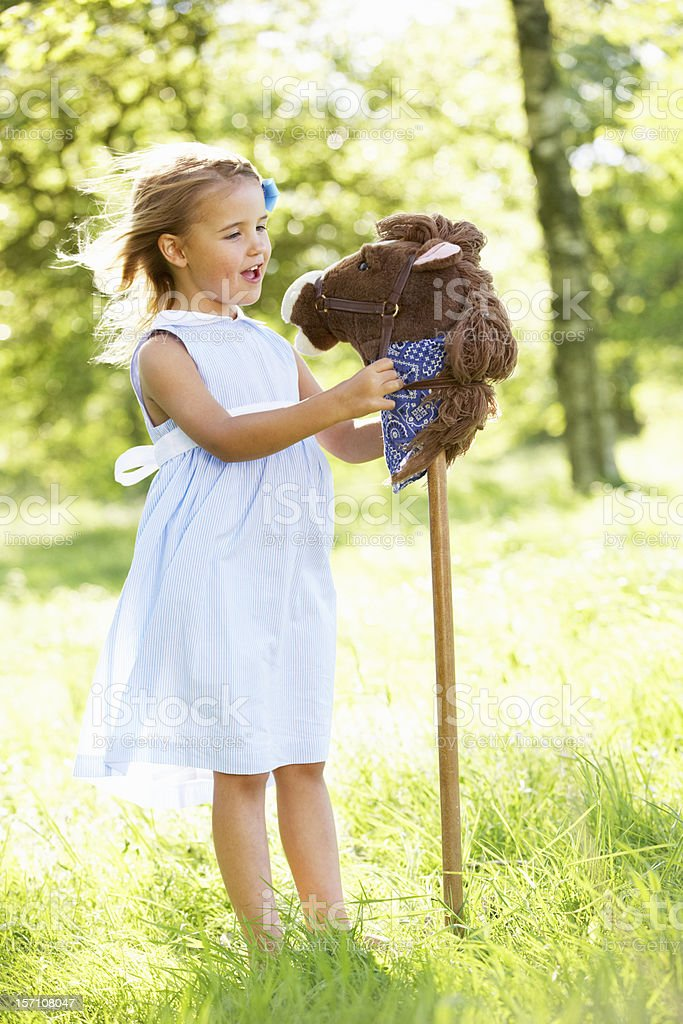 Young Girl Playing With Hobby Horse In Summer Field royalty-free stock photo