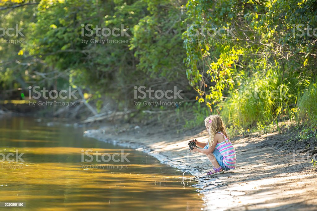 Young Girl Playing With Mud On River Bank stock photo