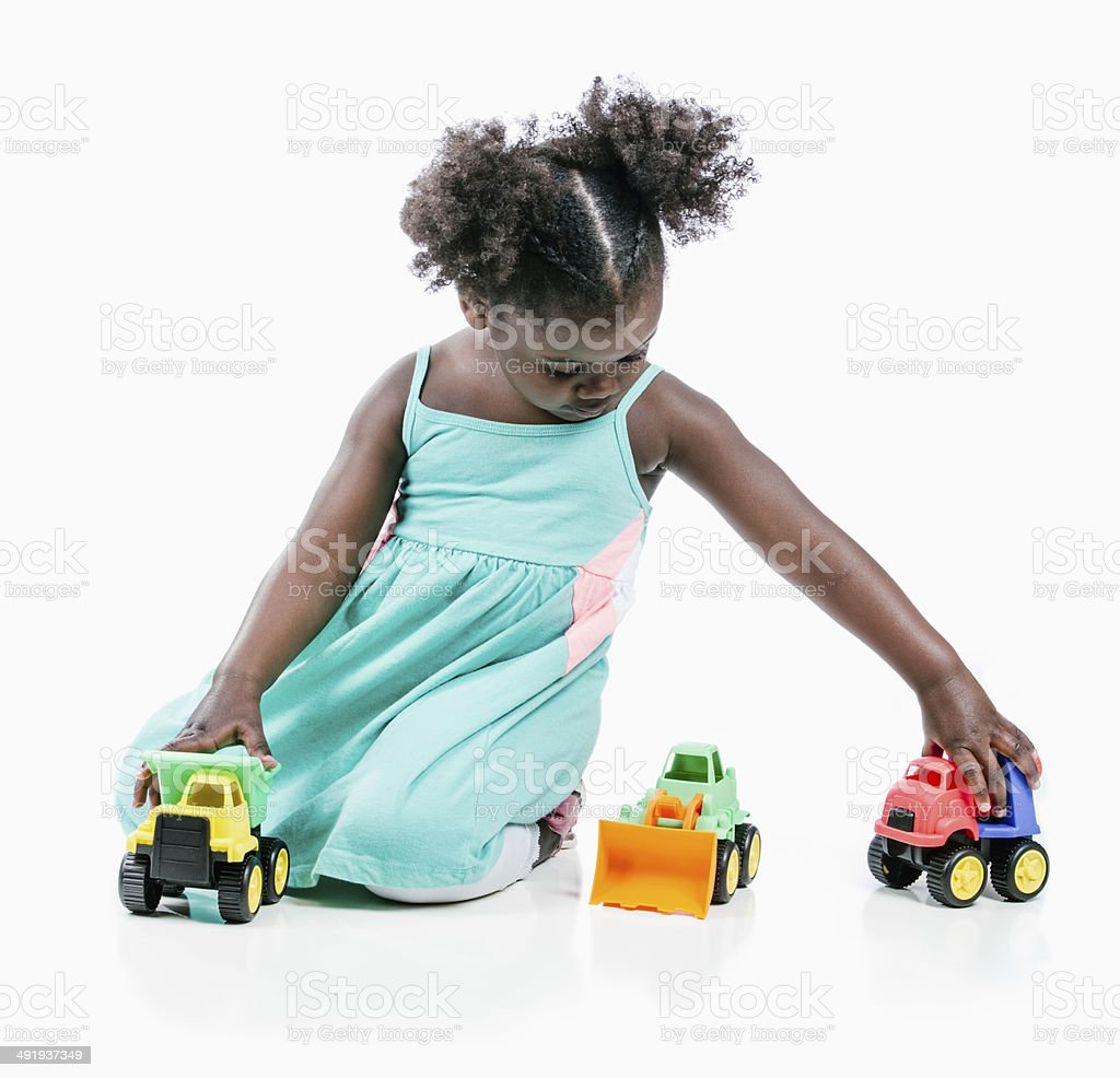Young girl playing with toy trucks wearing a blue dress stock photo