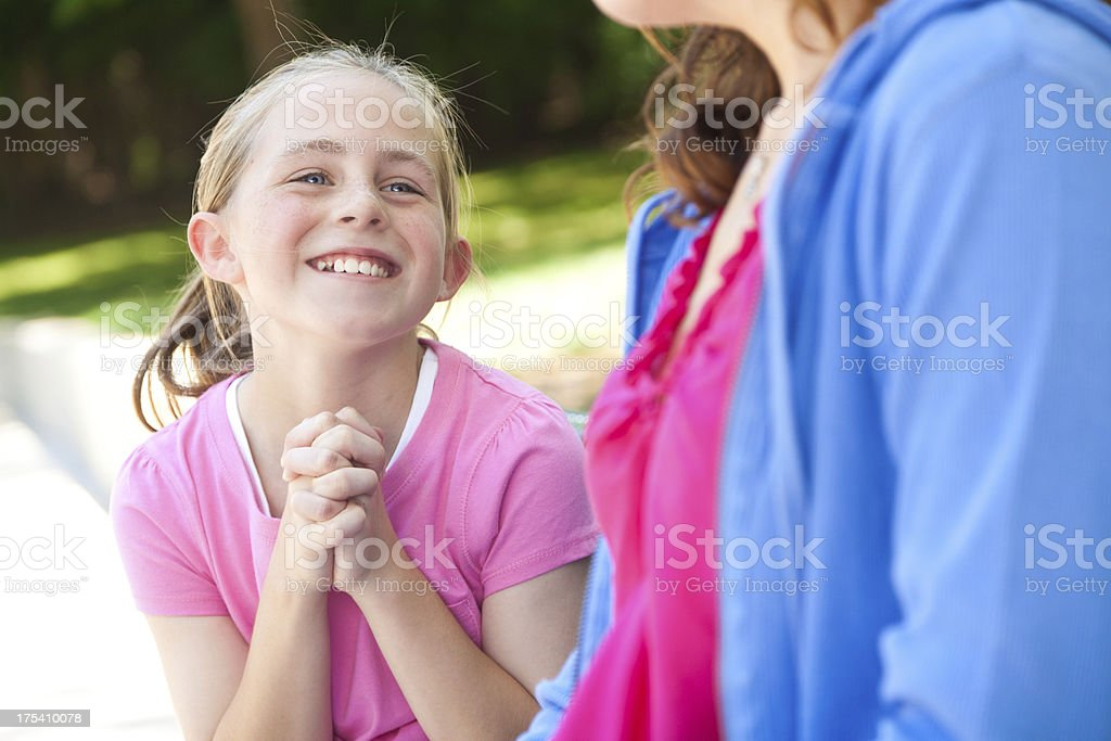 Young girl pleading with her mother for something stock photo