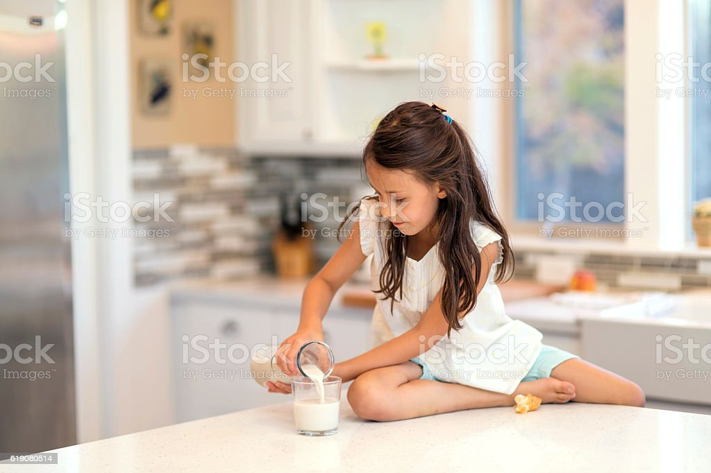 Young girl pours a glass of milk on the counter stock photo