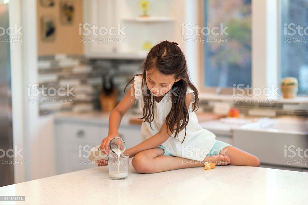 Young girl pours a glass of milk on the kitchen table stock photo