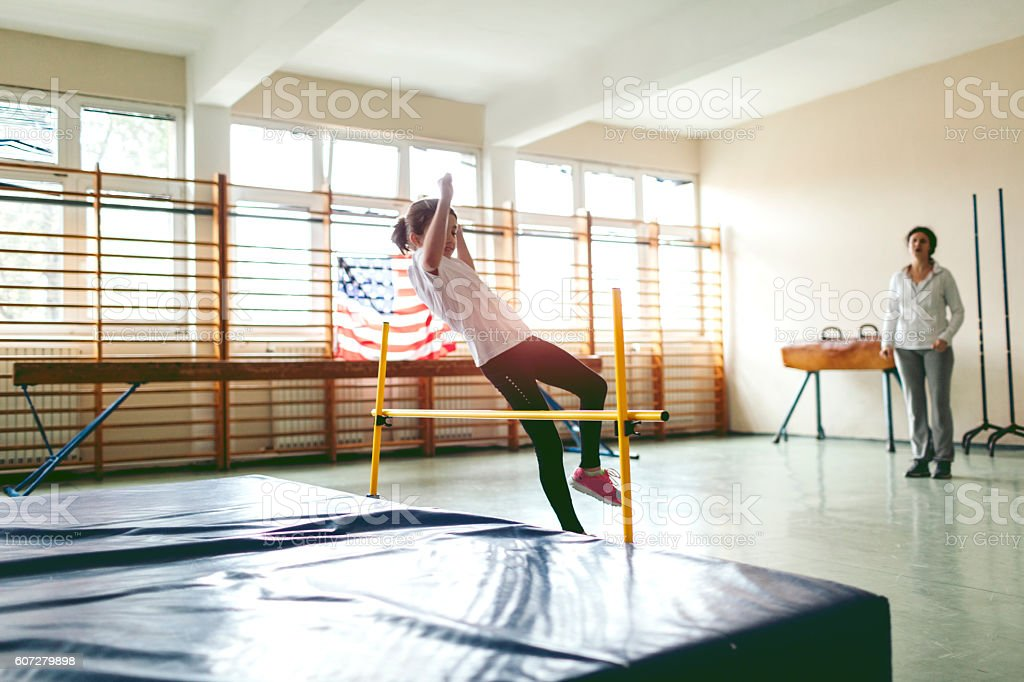 Young Girl Practicing High Jump Indoors. stock photo