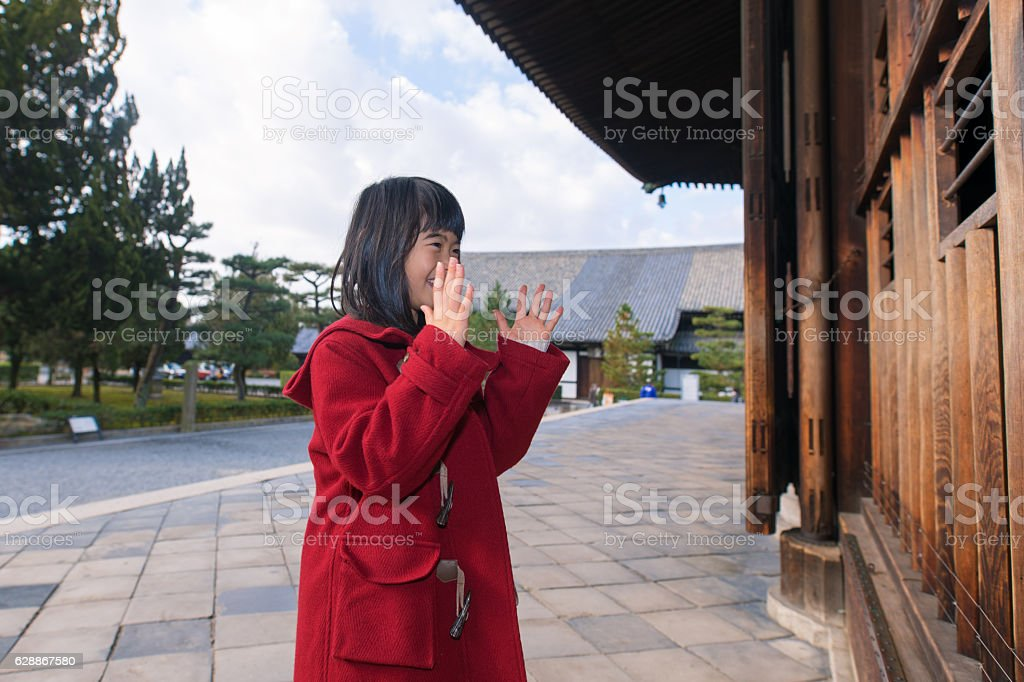 Young girl praying for peace in Tofukuji temple, Kyoto stock photo