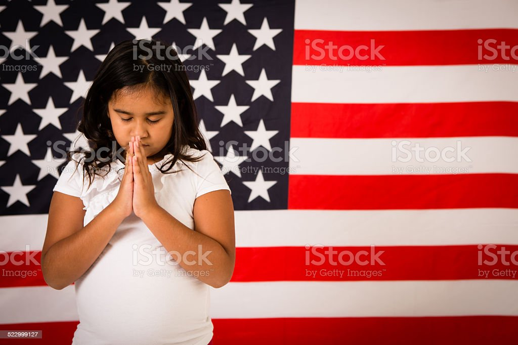 Young Girl Praying in Front of American Flag stock photo