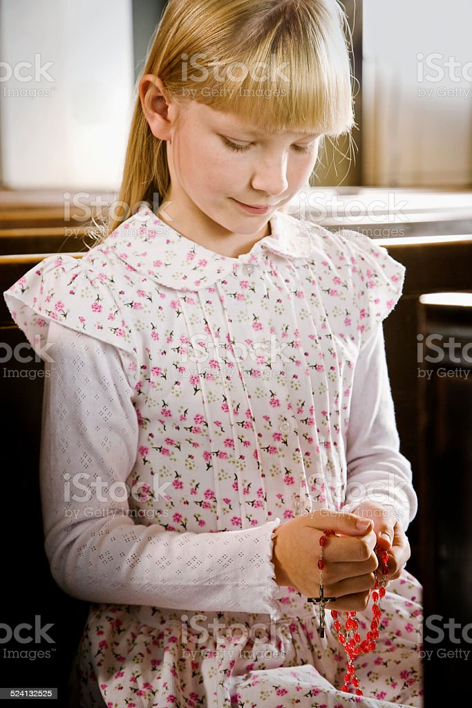 Young Girl Praying Rosary in Church stock photo