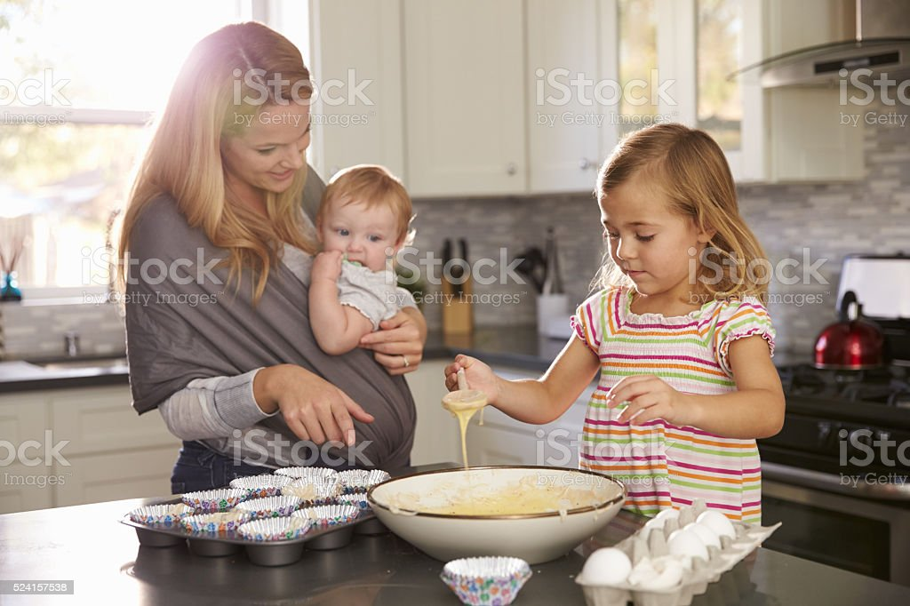 Young girl preparing cake mix in kitchen, mum showing baby stock photo