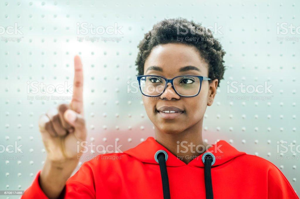 Young girl pushing virtual button stock photo